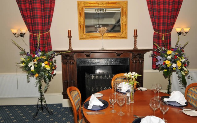 Grant Tartans in front of fire place